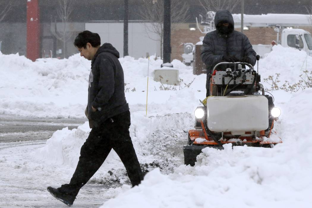 A pedestrian makes their way through a parking lot where snow is being cleared after an overnig ...