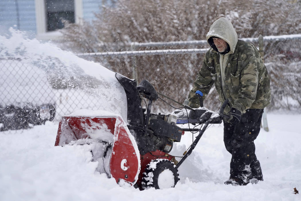 Keith Standring clears snow for The Alternative Living Center in Pittsfield, Mass., following a ...