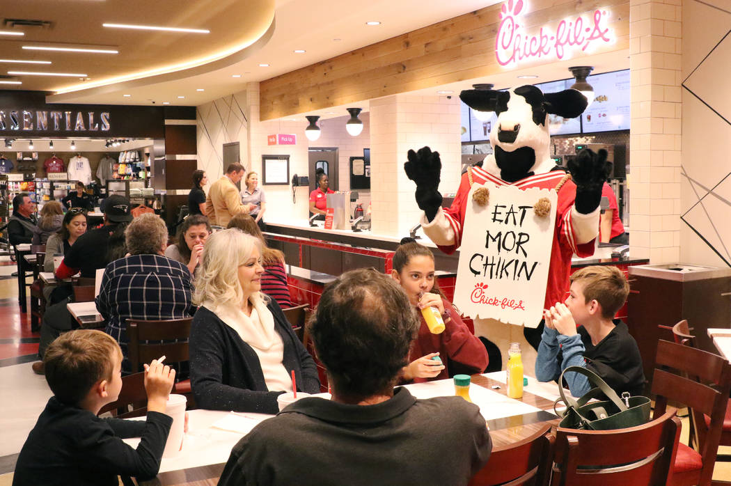 Chick-fil-A's mascot, the cow, greets customers at the first Chick-fil-A restaurant inside the ...