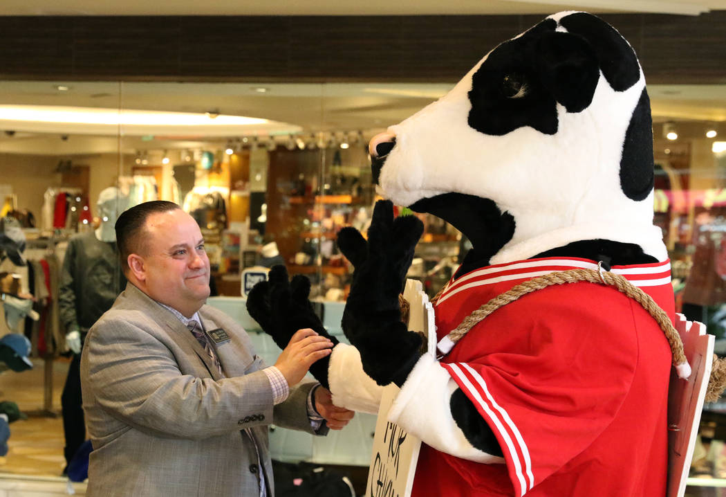 Scott Murray, general manager at Chick-fil-A, chats with Chick-fil-A's mascot, the cow, at the ...