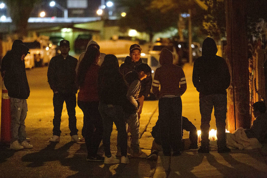 People gather to mourn a 17-year-old boy who was shot and killed near the 2600 block of Ferguso ...