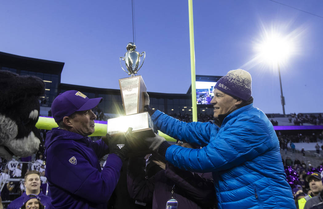 Washington Governor Jay Inslee hands Washington head coach Chris Petersen the Apple Cup after a ...