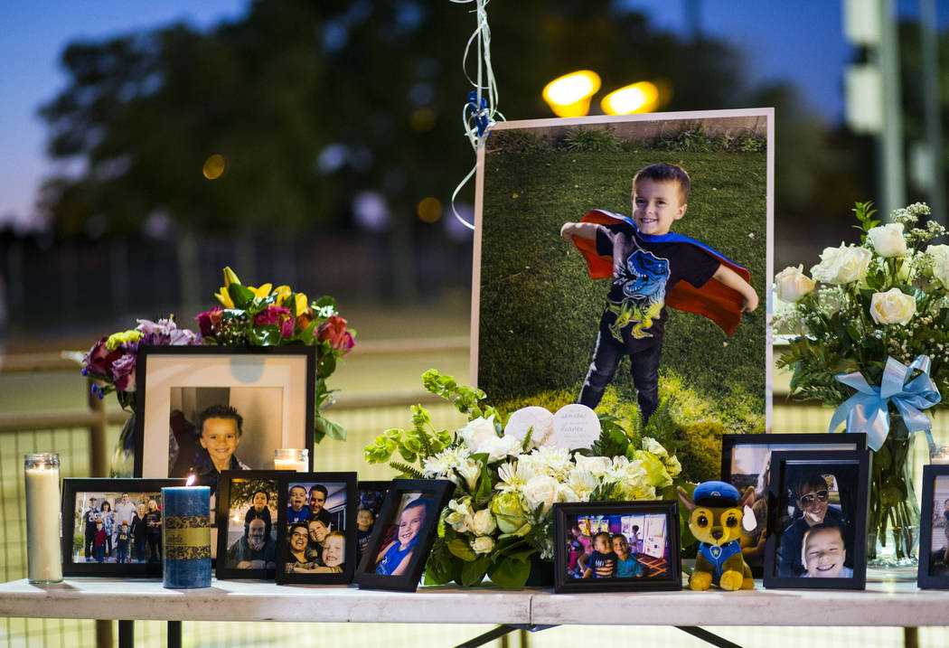 Photos of Gavin Murray Palmer, who was lost in a house fire, during a candlelight vigil in his ...