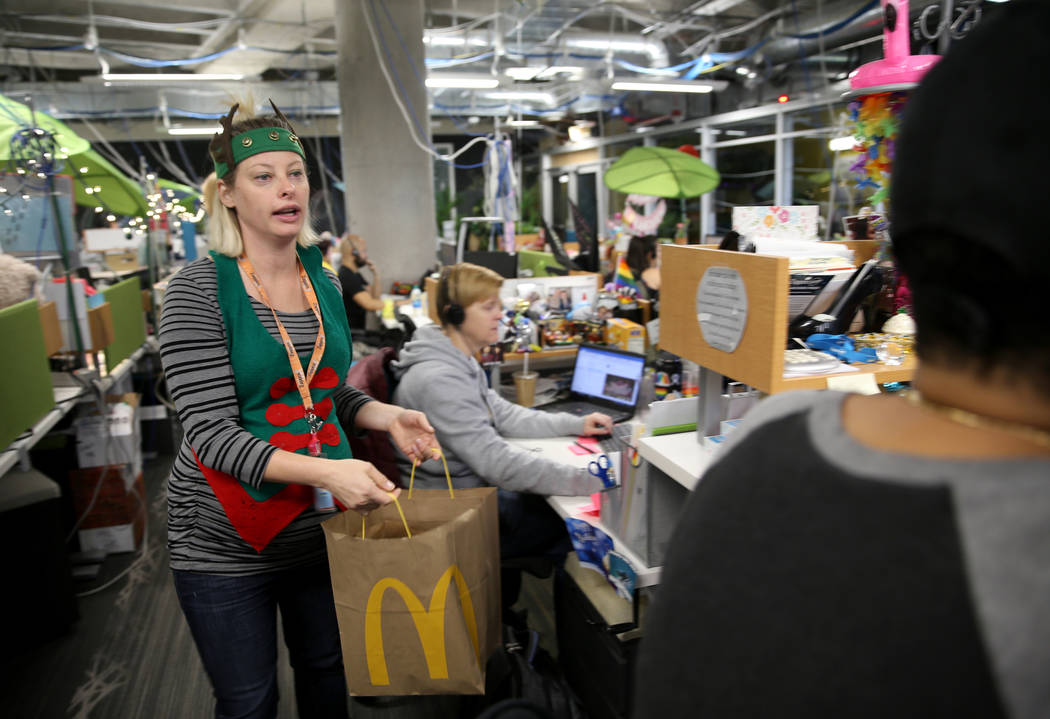 Zappos Customer Service Manager Jessica Hall hands out breakfast sandwiches at the company's he ...