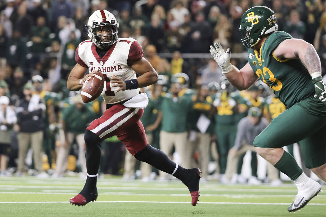 Oklahoma quarterback Jalen Hurts, left, rolls away from the pressure by Baylor defensive tackle ...