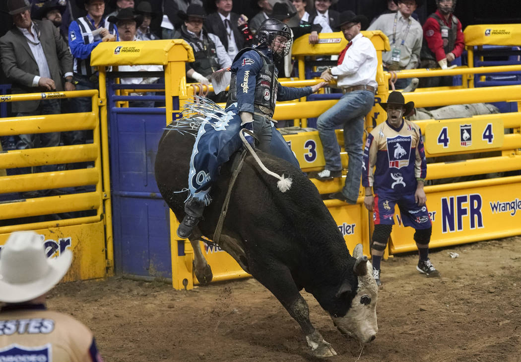Joe Frost of Randlett, Utah (103) competes in the bull riding event during the eighth go-round ...