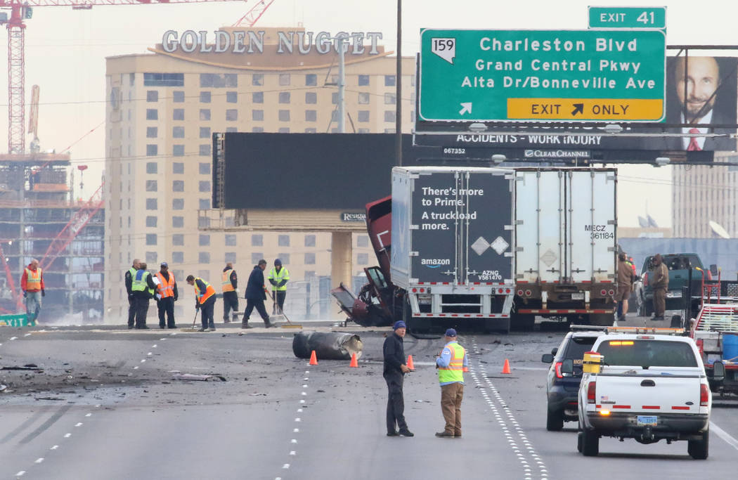 Workers clean-up debris after a fatal car crash where a wrong-way driver was killed on northbou ...