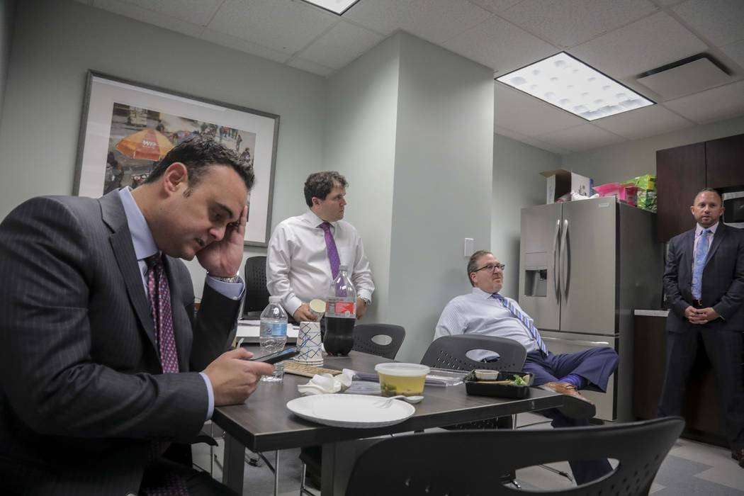 In a Tuesday, Oct. 29, 2019, photo, attorney Adam Slater, left, checks his phone during a worki ...