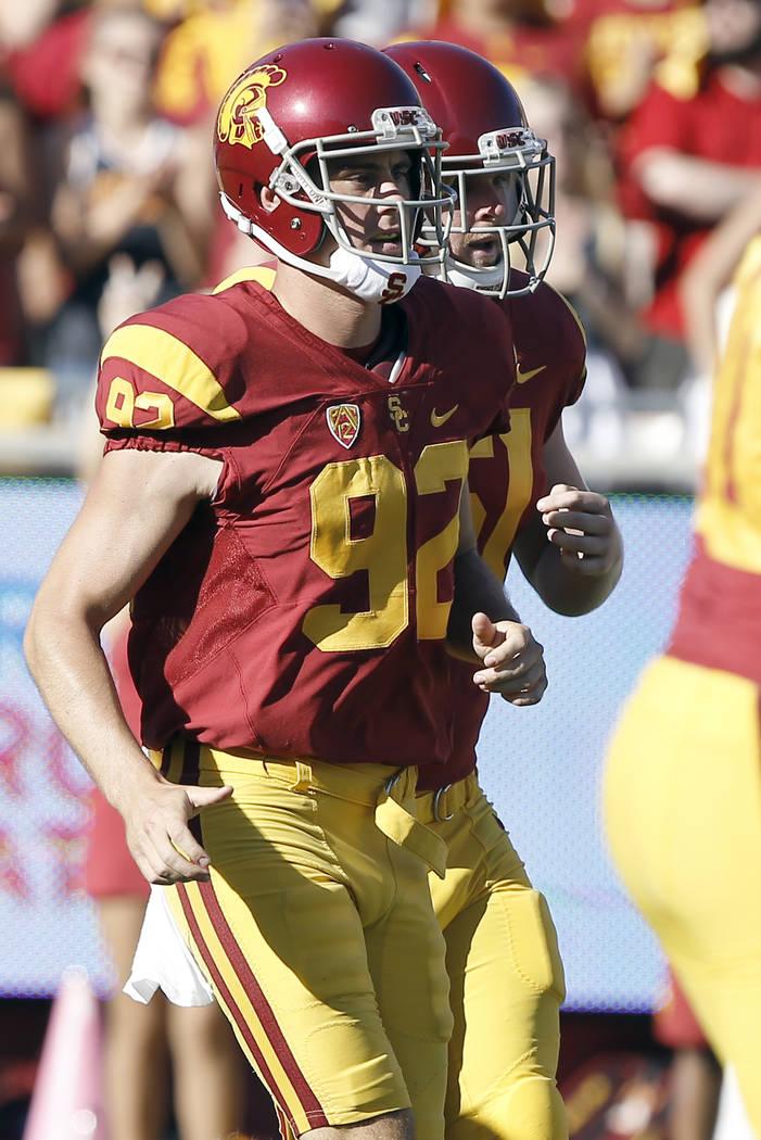 Southern California holder Wyatt Schmidt, left, runs on the field with blind long snapper Jake ...