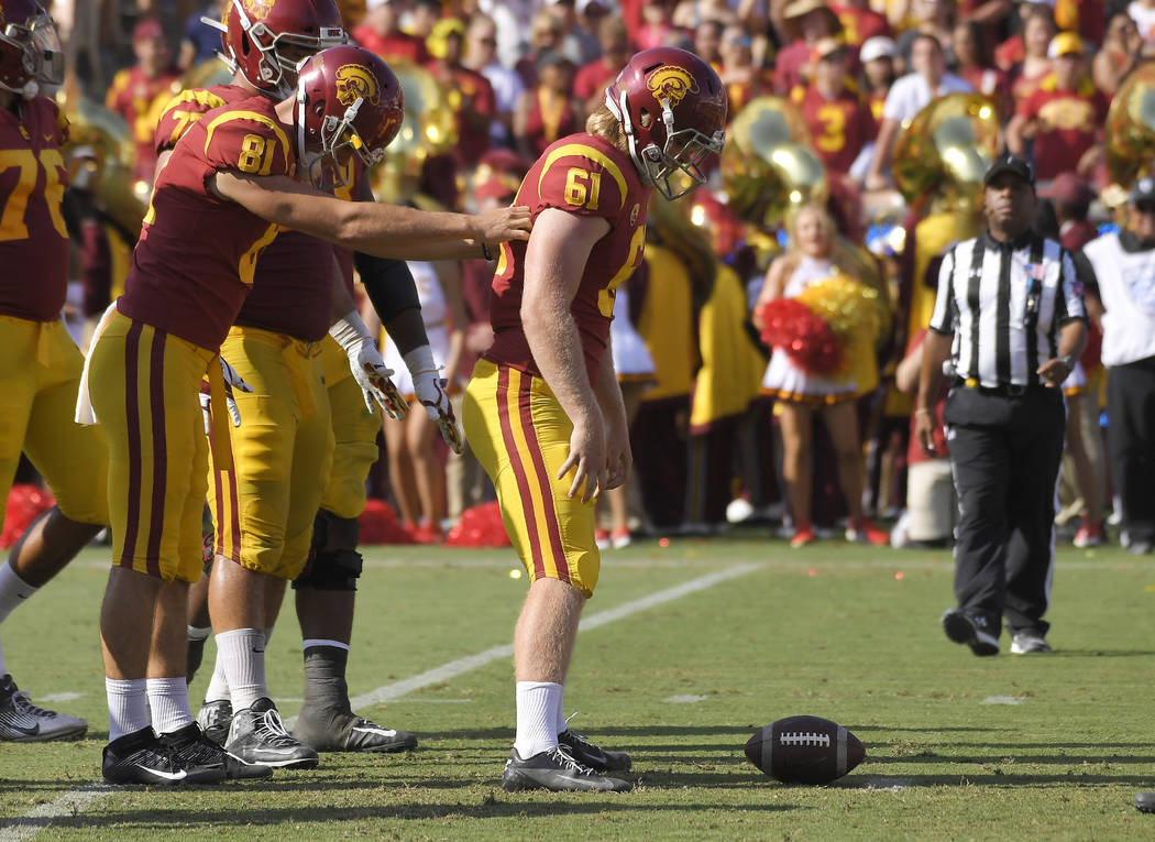 Southern California long snapper Wyatt Schmidt, left, helps long snapper Jake Olson, who is bli ...