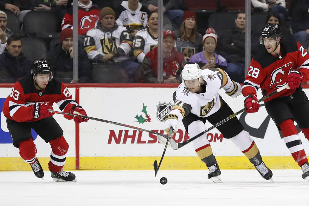 Vegas Golden Knights center William Karlsson (71) reaches for the puck as New Jersey Devils lef ...