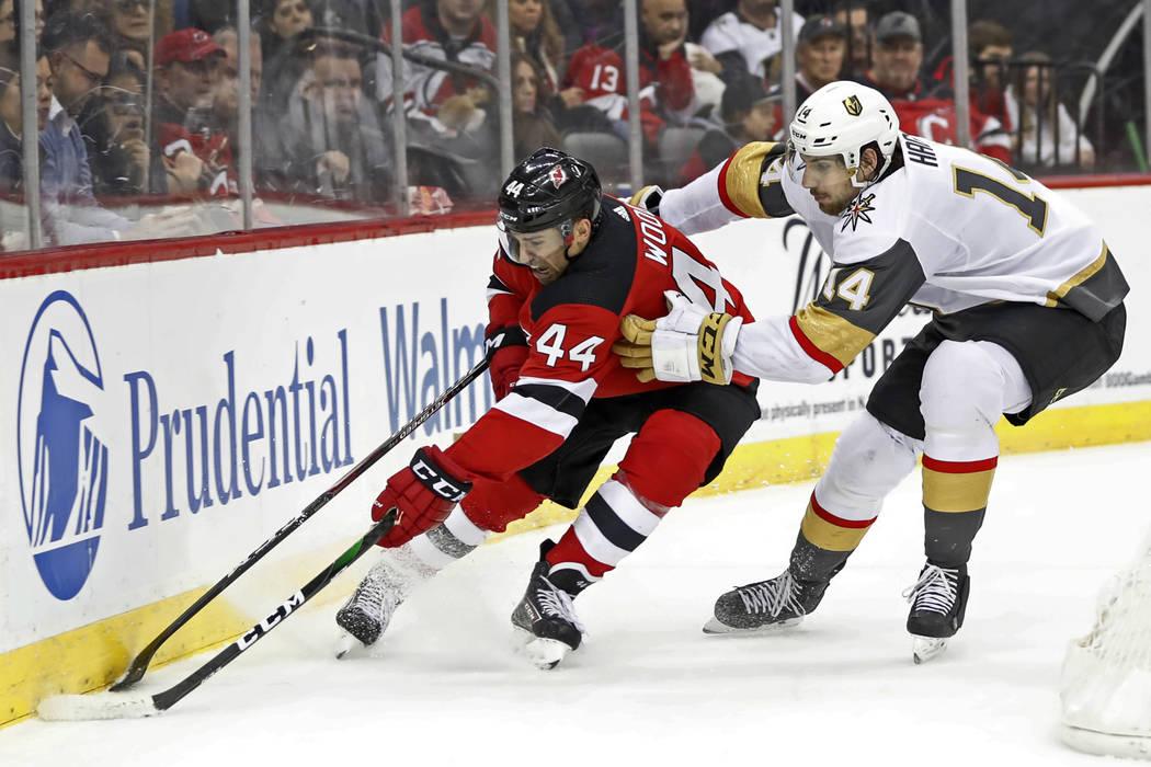 Vegas Golden Knights defenseman Nicolas Hague (14) gets his stick around New Jersey Devils left ...