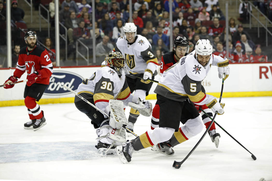 Vegas Golden Knights defenseman Deryk Engelland (5) tries to corral the puck away from New Jers ...