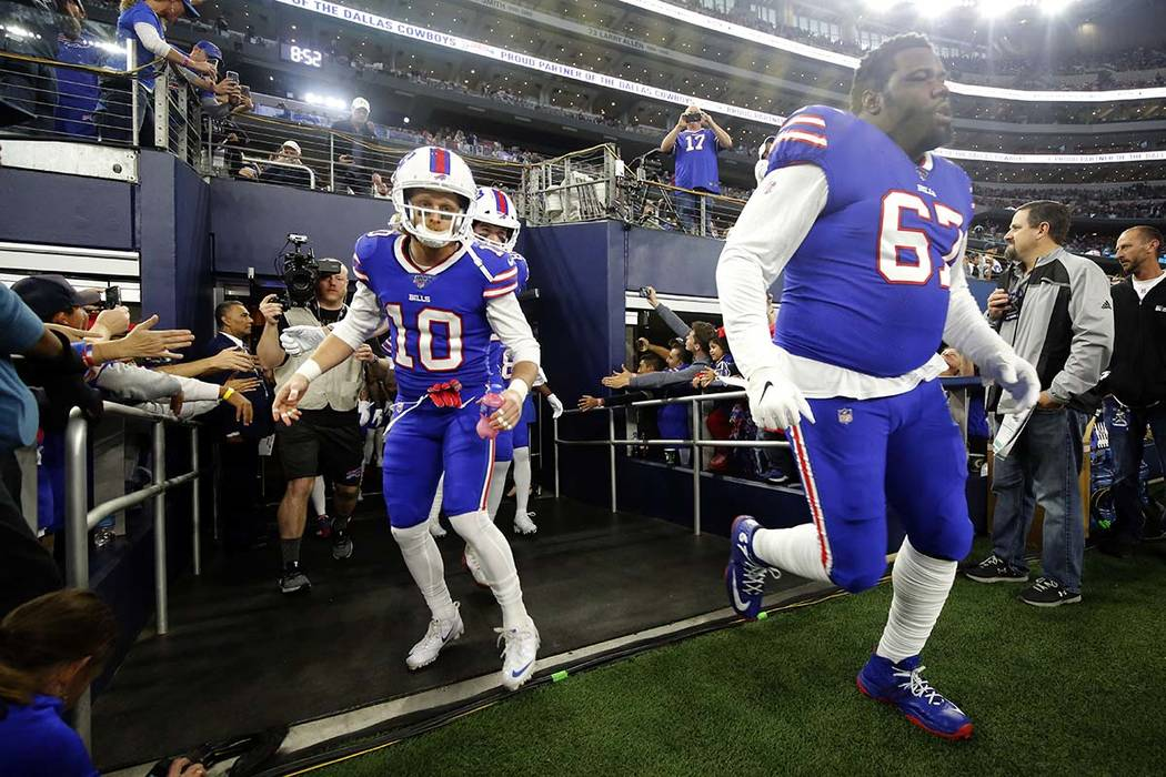 Buffalo Bills wide receiver Cole Beasley (10) and guard Quinton Spain (67) rush onto the field ...