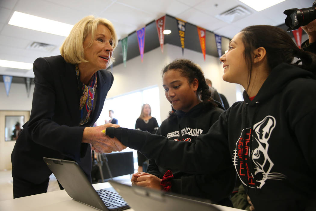 Secretary of Education Betsy DeVos, from left, speaks to 10th graders Sonaya Fernandes, 15, and ...