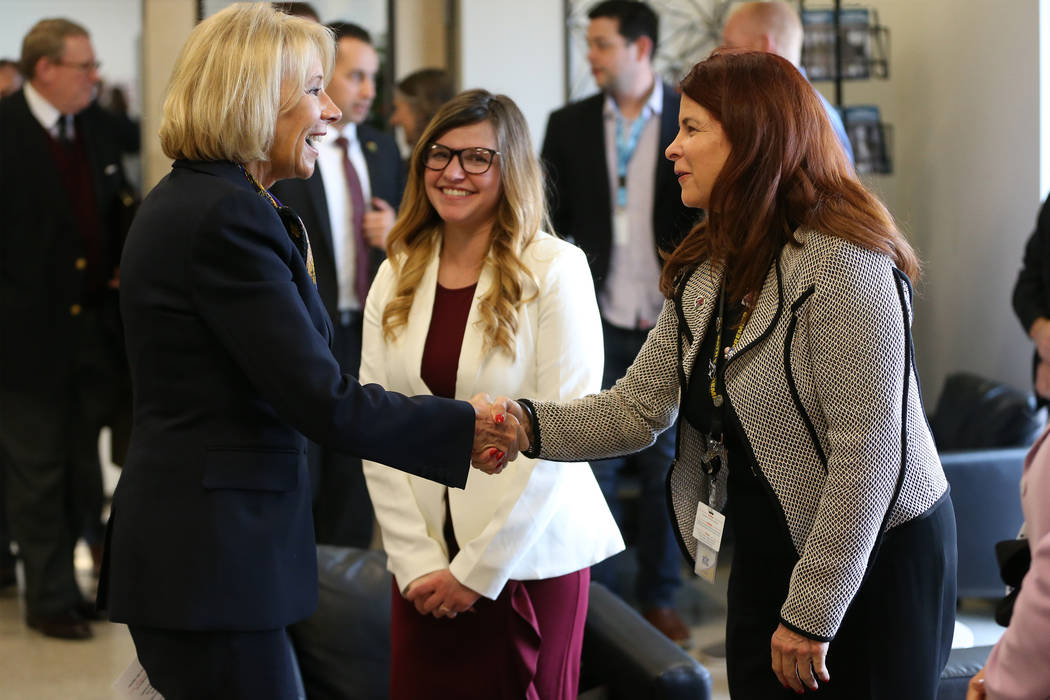 Secretary of Education Betsy DeVos, left, shakes hands with Henderson Mayor Debra March during ...