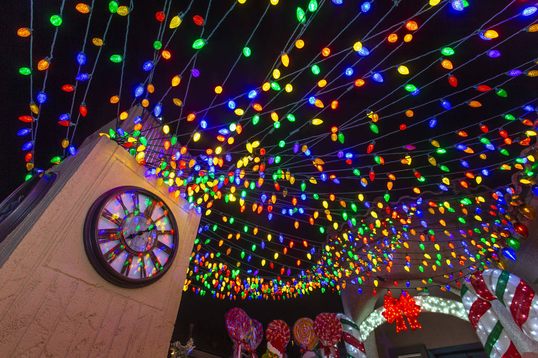A clock tower and strings of lights as part of the holiday lights display in the yard of Maria ...