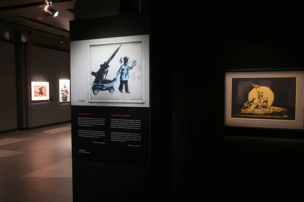 """Game of War,"" left, and ""Flag (Gold)"" on display in ""Banksy: Genius o ..."