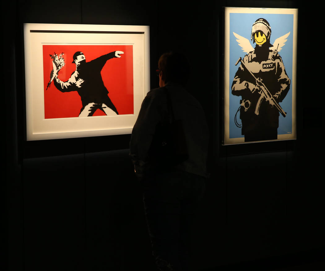 "Kim Thompon of Atlanta checks out ""Rage, Flower Thrower,"" left, and ""Flying Copp ..."