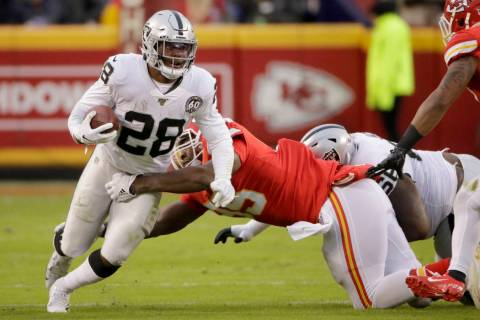 Oakland Raiders running back Josh Jacobs (28) tries to break a tackle by Kansas City Chiefs def ...