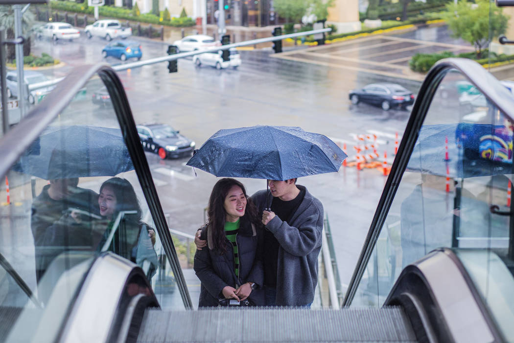 Tourists from Seoul South Korea Lee Hyemin, left, and An Jinoh, huddle under an umbrella as th ...