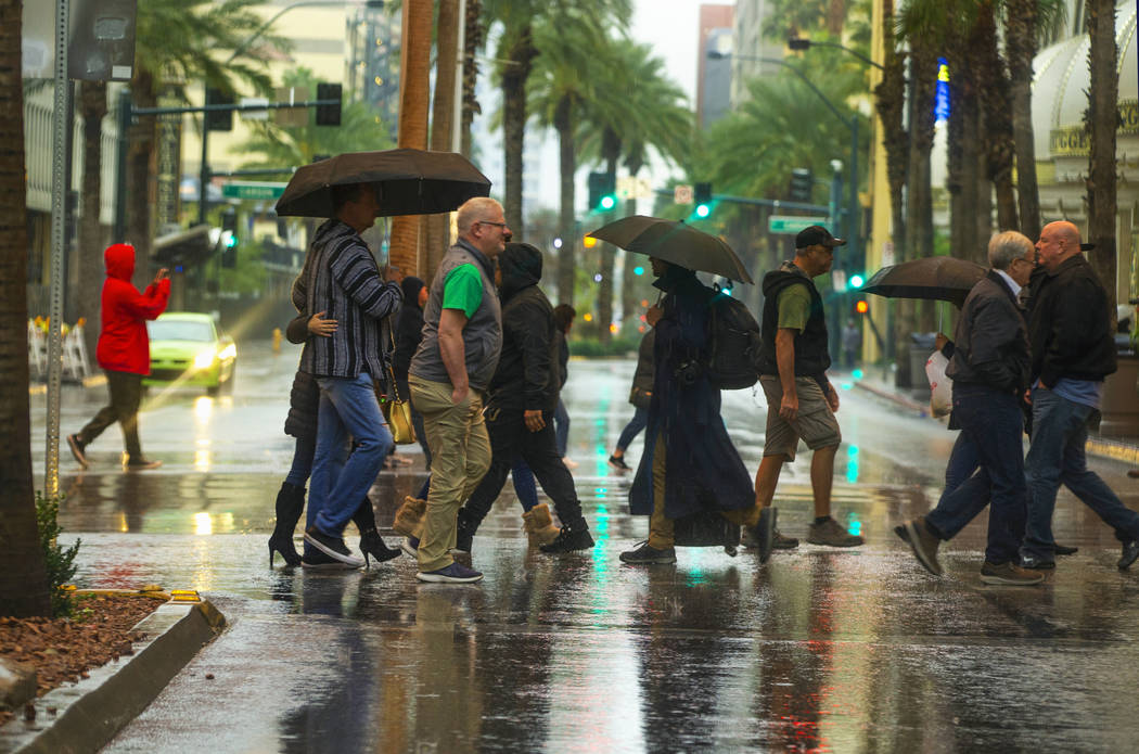 People cross the street on a rainy day about the Fremont Street Experience and South 3rd Street ...