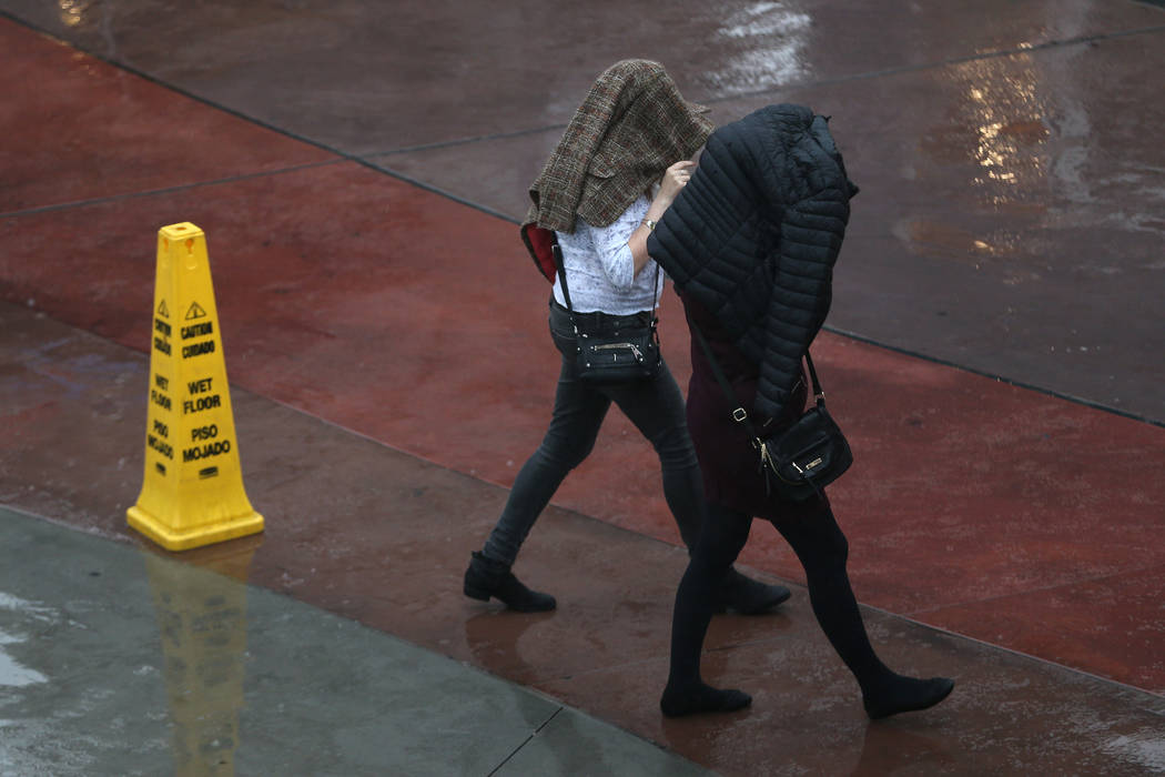 People walk in the rain at the Strip near Bally's casino-hotel in Las Vegas, Wednesday, Dec. 4, ...