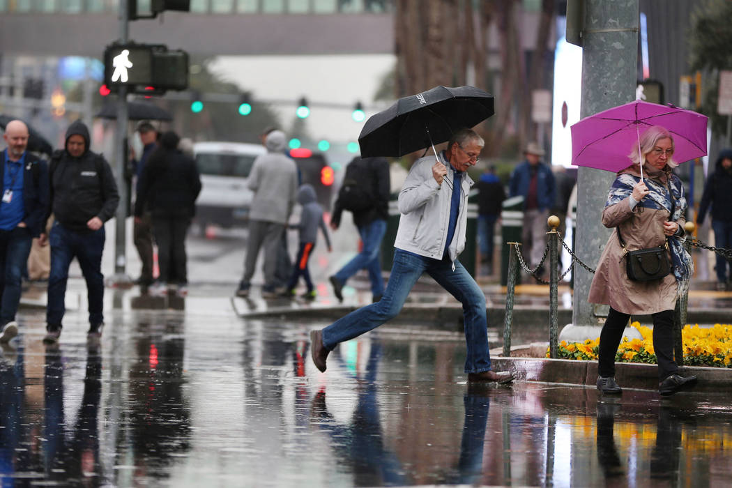People walk a flooded intersection across from the Planet Hollywood casino-hotel in Las Vegas a ...