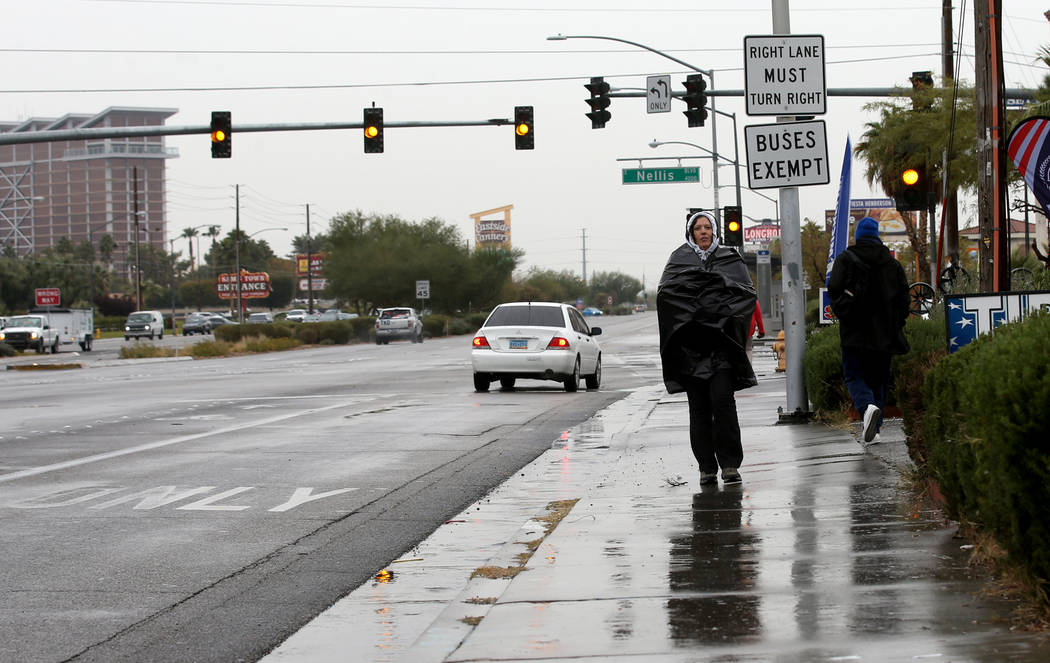 Penny Curiel stays dry under a plastic bag on Boulder Highway at Nellis Boulevard in Las Vegas ...