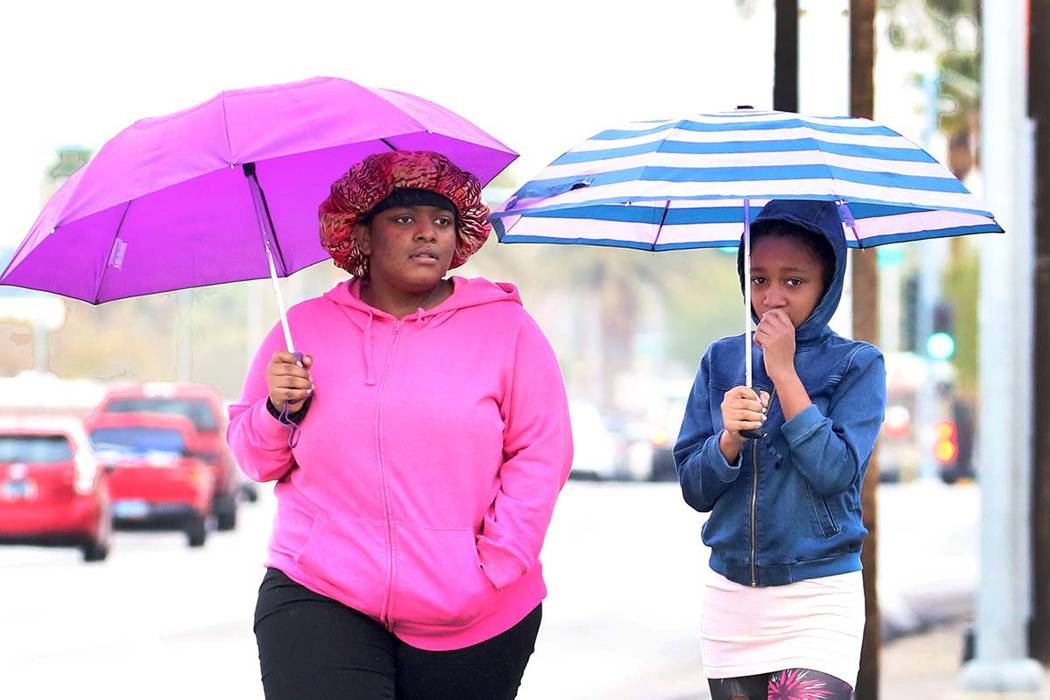 Pedestrians hold umbrellas to protect themselves from rain as they walk along Las Vegas Bouleva ...