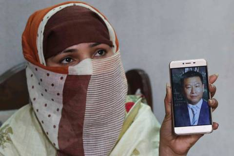 In a May 22, 2019, file photo, Sumaira a Pakistani woman, shows a picture of her Chinese husban ...