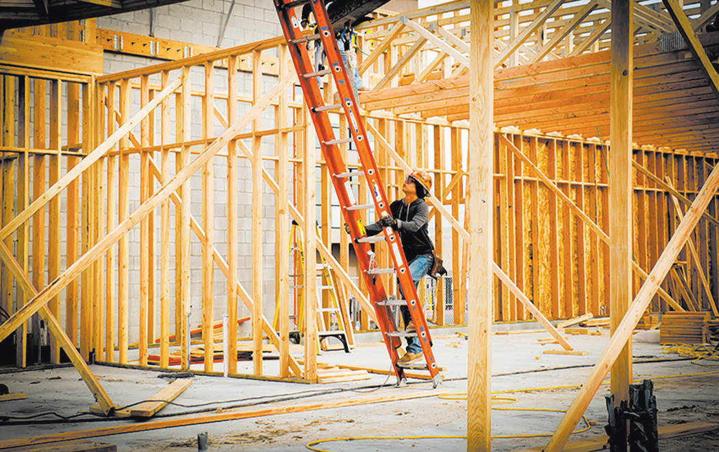 A worker climbs a ladder at a new-home construction site. Valley homebuilders say prices will c ...