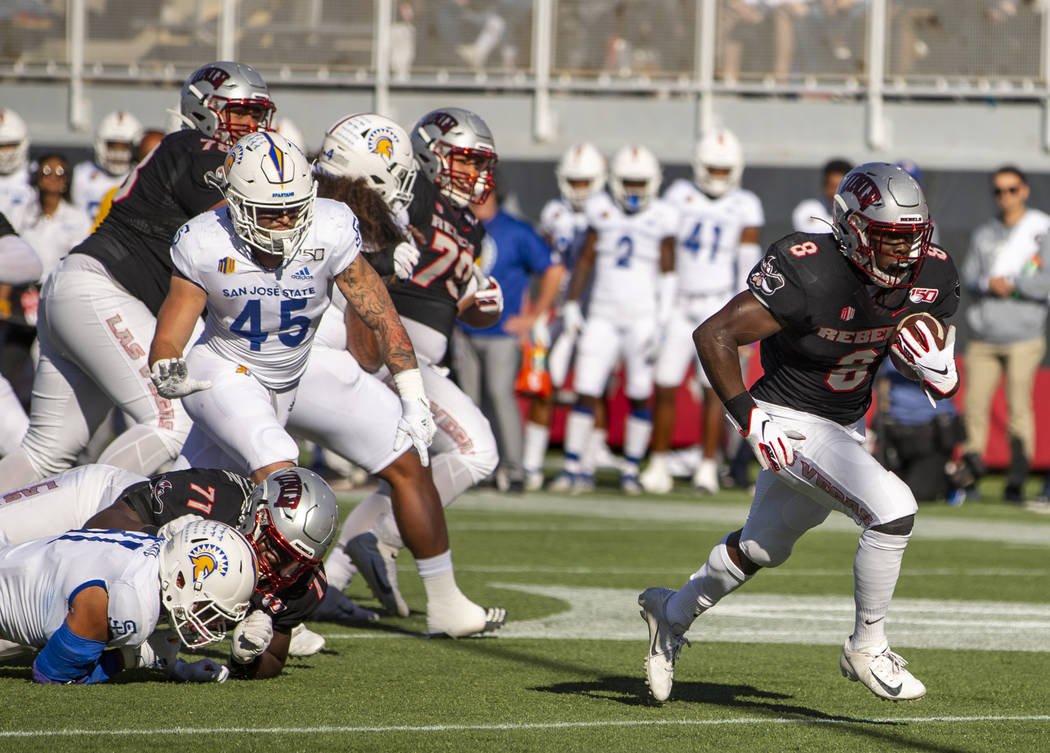 UNLV Rebels running back Charles Williams (8, right) breaks free of the San Jose State Spartans ...