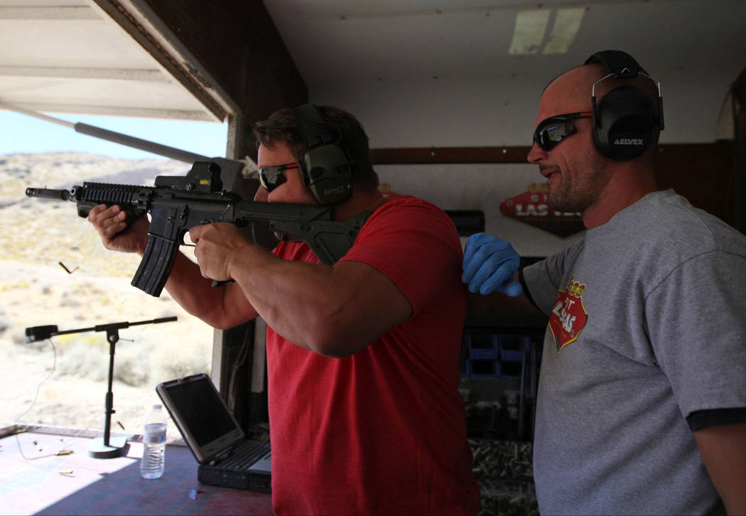 Carl Bunce, left, learns how to handle an automatic weapon from Shoot Las Vegas firearm instruc ...