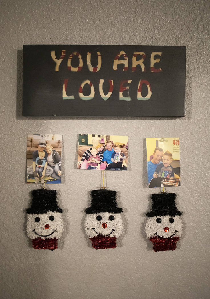 Family photos of Joan Williams, Dustin Huebner, and their sons John and Chase Huebner adorn the ...