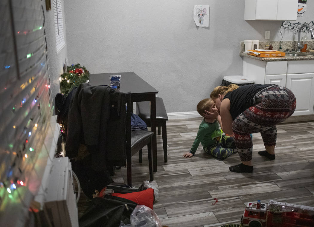 Joan Williams kisses her son, Chase Huebner, 6, in their new one-bedroom apartment on Saturday, ...