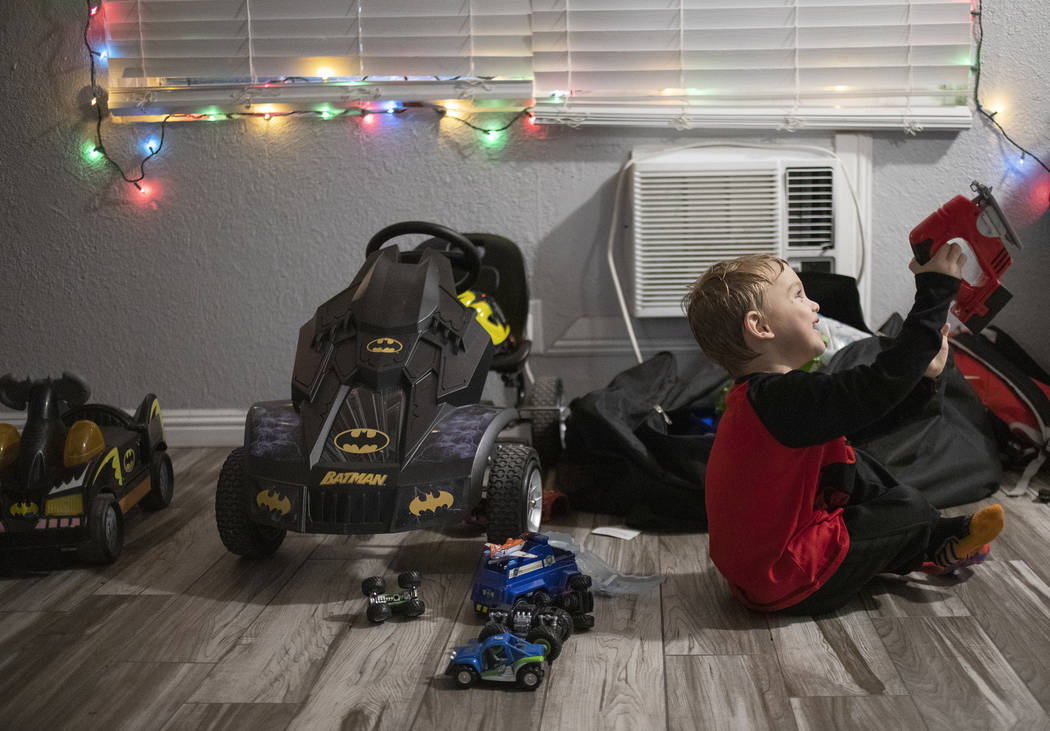 John Huebner, 2, plays with toys at his mom's new apartment on Saturday, Dec. 14, 2019, in Las ...