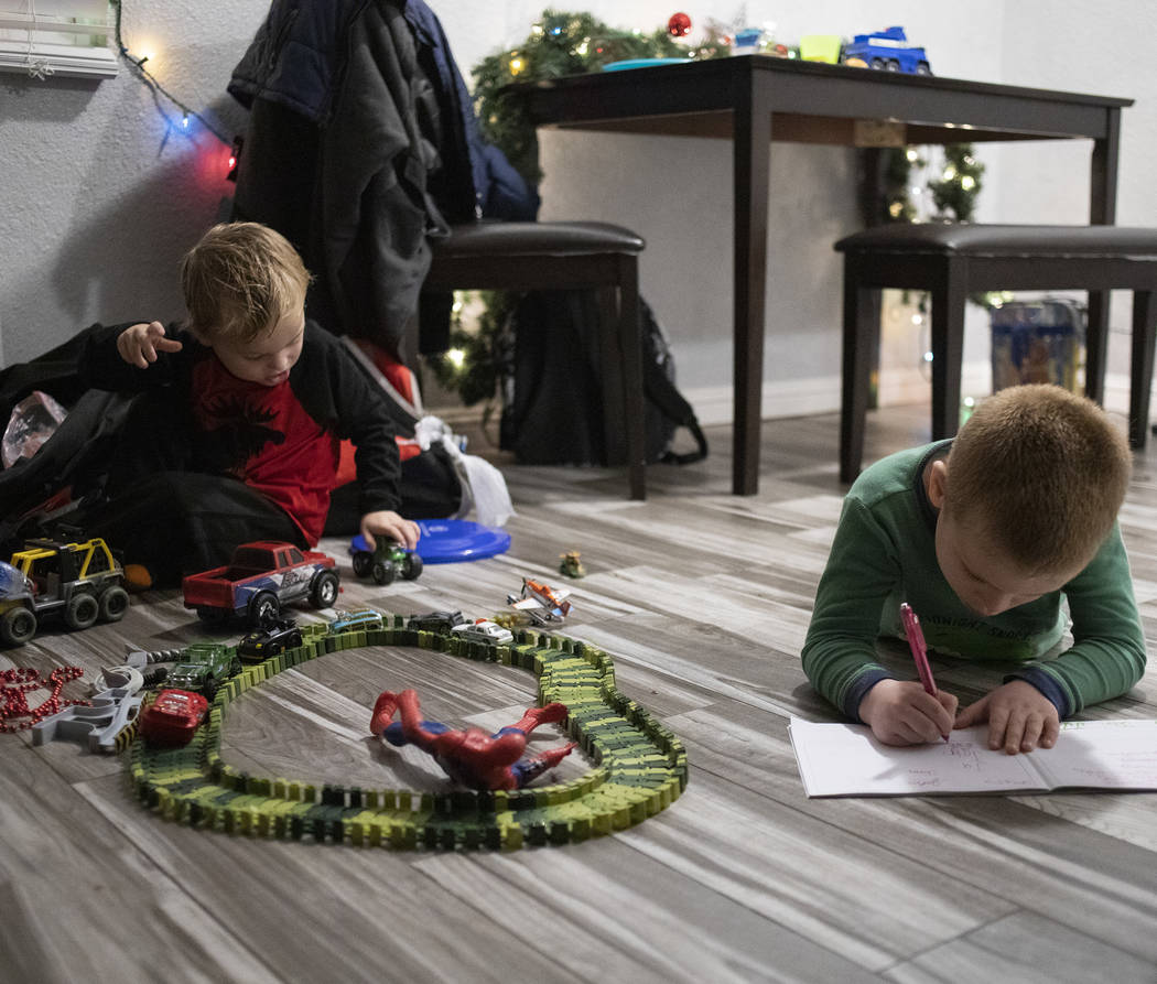 John Huebner, 2, left, plays with toy cars as Chase Huebner, 6, right, works on his schoolwork ...