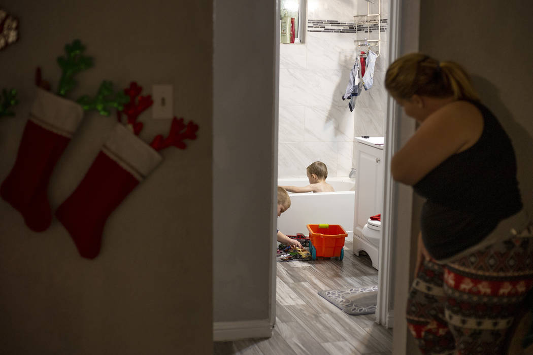 Joan Williams looks on as her sons Chase Huebner, 6, and John Huebner, 2, play in the bath duri ...