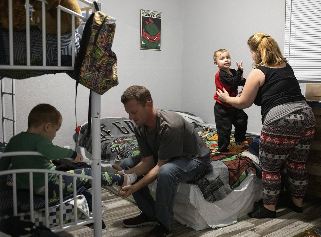 Dustin Huebner, second from left, helps his son Chase Huebner, 6, left, put on his pajamas as J ...