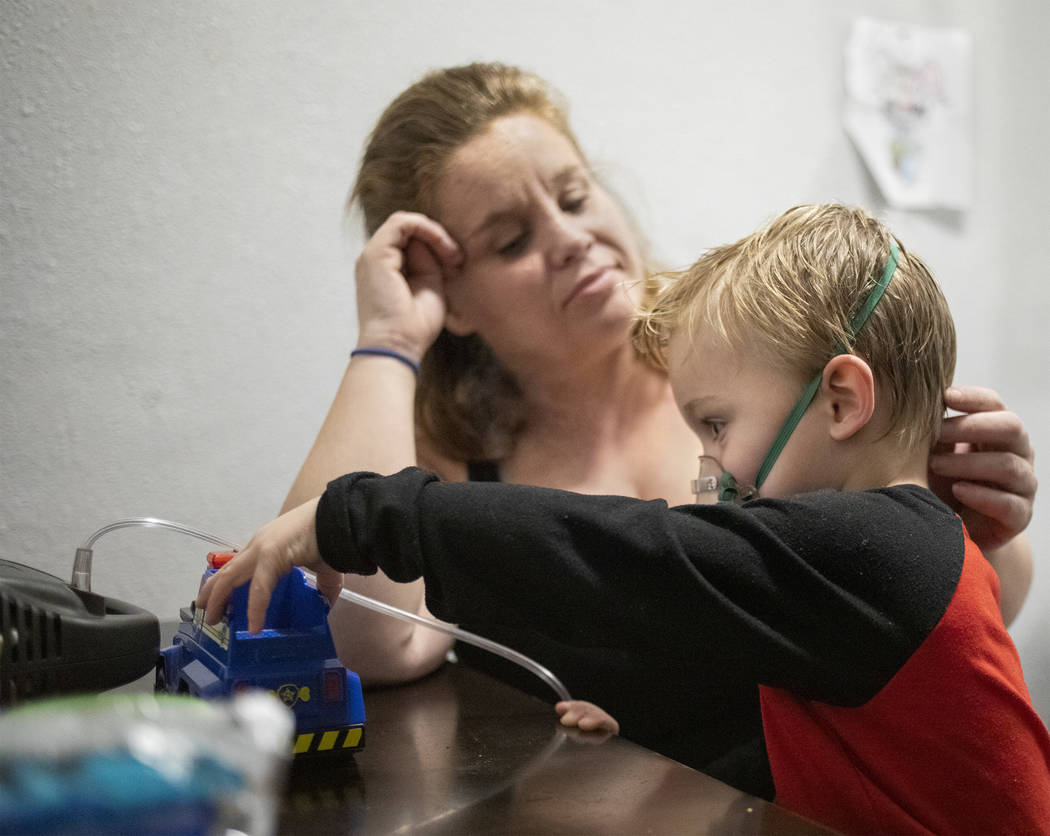 Joan Williams, left, watches as her son, John Huebner, 2, right, plays while receiving his lung ...