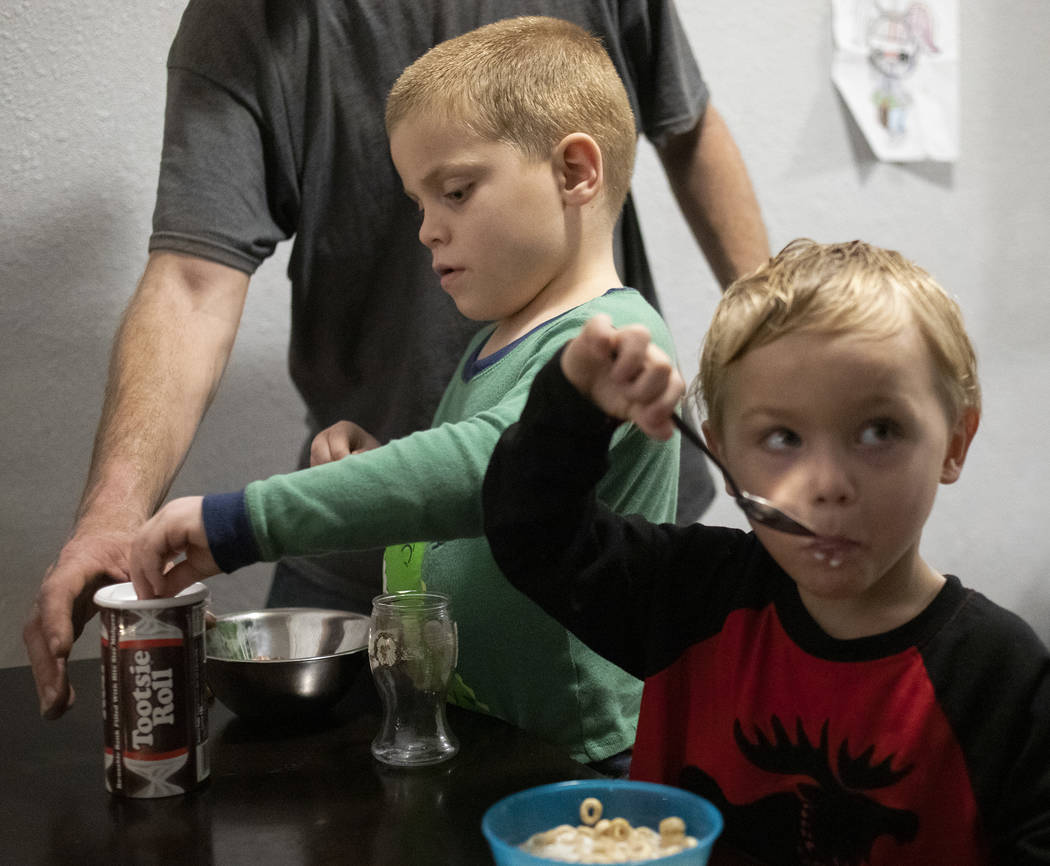 Dustin Huebner reaches to help his son, Chase Huebner, 6, left, fill his piggy bank as his othe ...
