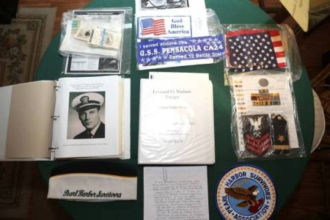 Items belonging to Leonard Nielsen, a 93-year-old Pearl Harbor survivor, are displayed on a tab ...