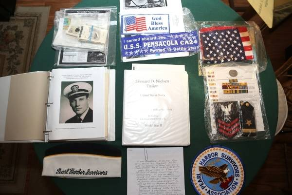 Items belonging to Lenoard Nielsen, a 93-year-old Pearl Harbor survivor, are displayed on a tab ...