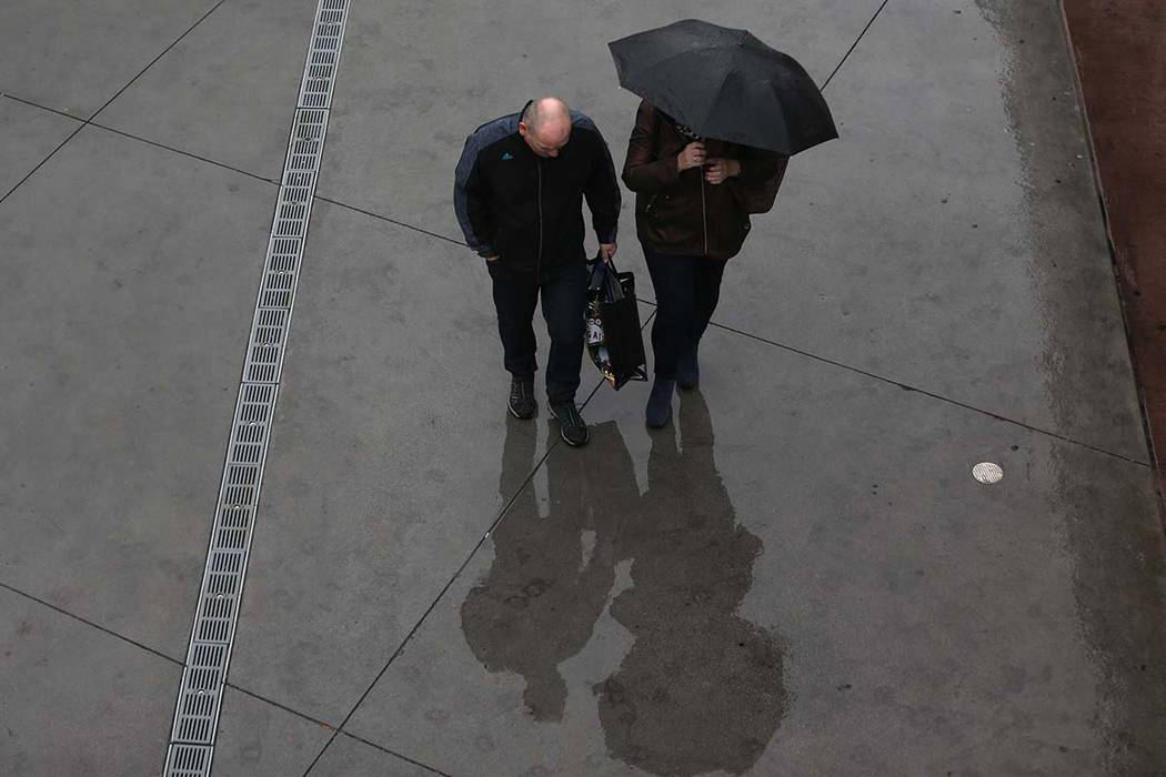People walk in the rain at the Strip near Bally's casino-hotel in Las Vegas, on Wednesday, Dec. ...