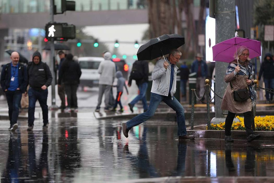 Some puddle-jumping is involved as people cross a flooded intersection across from Planet Holly ...