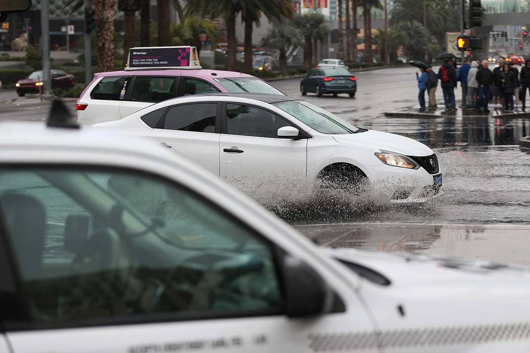 Drivers make their way to the Bellagio casino-hotel in Las Vegas on a flooded intersection as r ...
