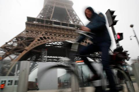 A man rides his bicycle in front of the closed Eiffel Tower in Paris, Thursday, Dec. 5, 2019. T ...
