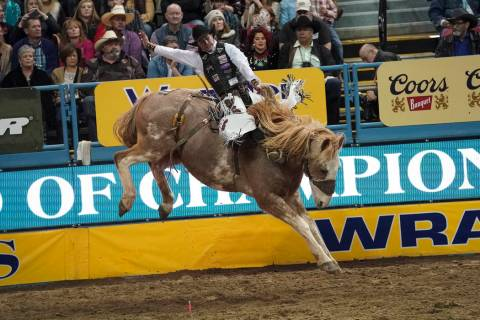 Chase Brooks of Deer Lodge, Mont. (111) competes in the saddle bronc riding event during the ei ...