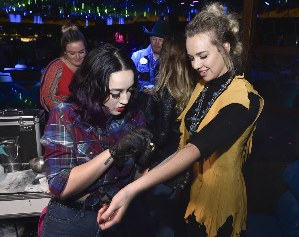 An attendee receives a temporary tattoo during the WNFR Party With Abandon at the Ling Ling Clu ...